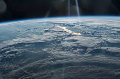 Clouds and golden sun glint photographed from low Earth orbitJune 9, 2016 Beams of Light on a Golden Lake
