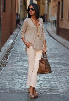 Classic beige blouse, cream pants, brown large handbag, and open toe beige heels accessorized with long gold necklace andn bracelets