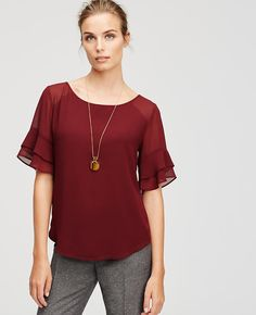 Sheer beauty: pairing feminine flounce with rich fall colors, our tiered ruffle sleeve style is a top pick in the season's most-wanted shades and prints. Scoop neck. Short ruffle sleeves. Front and back shoulder yoke. Back keyhole with button closure. Shirttail hem. Lined body.