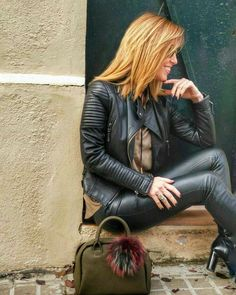 Blonde in ribbed black leather jacket pants and ankle boots