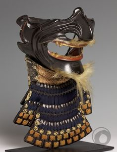 Shikami menpô Mid Edo Period (1615-1867) Samurai armour's mask Nerigawa (lacquered leather) A very good leather mask lacquered in black with red and gold details. The production of nerigawa is actually more difficult than the production of iron masks. The yodare-kake is mad of individual nerigawa plates (hon-kozane) The mask, with long teeth, a fierce expression and a long nose, represents a shikami demon