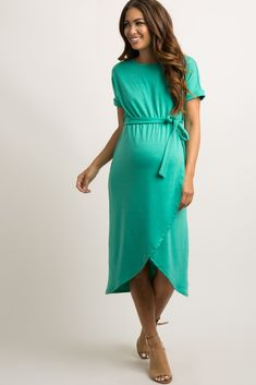 A solid hued maternity midi dress featuring a wrap front skirt, a cinched elastic waistline with a sash tie, short dolman sleeves, and a rounded neckline. This style was created to be worn before, during, and after pregnancy.