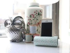 Cover a toilet paper roll with decorative scrapbook paper for an (almost) free DIY iPhone holder.