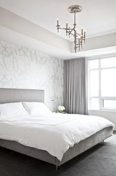 Modern silver gray bedroom with silver metallic wallpaper accent wall, gray linen modern bed, crisp white hotel bedding with white stitching, lilac gray curtains window panels and polished nickel winding Omega Chandelier.
