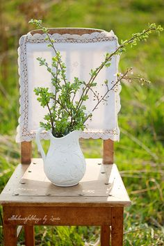 Rustic wedding décor: chair with lace back & pitcher of branches with leaves and little buds