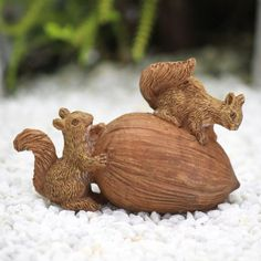 Fairy garden squirrels collecting nuts for winter