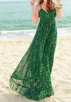 Full-length front view of model wearing green printed maxi dress at the beach