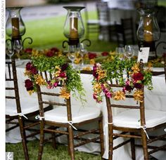 Garlands of flowers in the wedding's rich, warm palette of golds, saffrons, oranges, and deep reds hung from the newlyweds' brown chiavari chairs at the reception.