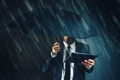 Businessman reading business news on digital tablet under umbrella in heavy rain.
