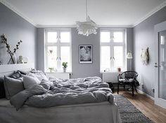 Schlafzimmer in Grau/Weiß mit kuschligen Decken und Bildern über dem ...