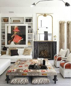 Large picture framed hanging on book shelves.  Love the hint of bohemian vibe in the ottoman