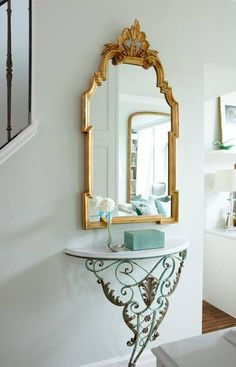 CREATE A STYLISH AD-HOC ENTRY FEATURE: In this case, a shallow wall-mount iron console below a pretty gold-toned mirror introduces the illusion of extra space