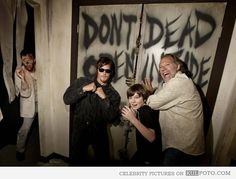 The Walking Dead behind the scenes - Norman Reedus aka Daryl Dixon posing with Chandler Riggs aka Carl Grimes by the Dont Open Dead Inside door in The Walking Dead behind the scenes photo.