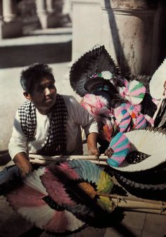 A woman sits selling feather fans as souvenirs to visitors in Siam, May 1934.Photograph by Jules Gervais Courtellemont, National Geographic