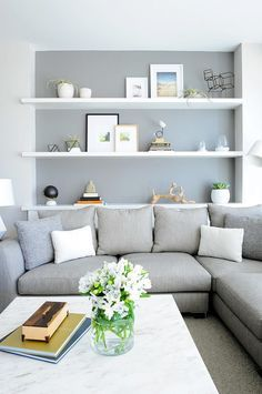 Neutral living room with gray sofa and feature wall with white shelves and leaning artwork