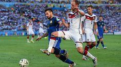 Benedikt Hoewedes of Germany (4) challenges Ezequiel Lavezzi of Argentina (22).