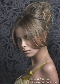 This up-style truly is a crown of hair made for the sultry princesses of today. With a fairly simple and neat front section, the tousled, airy creation that reaches up high in the back becomes even more exotic. A middle part and long bangs, gently rounded and sweeping along the sides smoothly lead the eye to the highlight of this style. The golden blonde color has darker and lighter sections that make this style look very lively and full of radiant dimension.