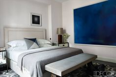 The master bedroom of this Paris apartment are light and airy with plenty of windows and doors, allowing designers Laurent Champeau and Kelli Wilde to get away with an oversized, deep blue art piece.   - ELLEDecor.com