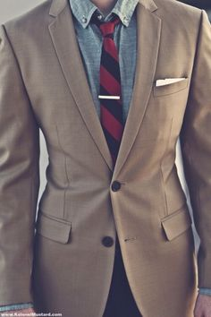 caramel colored suit. light denim shirt. red + navy tie. white pocket square. tie bar. great combo. style.