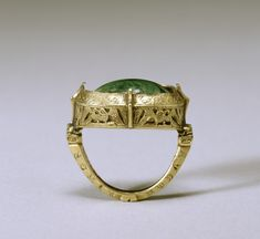 "This elaborate bishop's ring has the typical combination of a gold setting with a single, large stone, in this case malachite. The gold is decorated with openwork eagles, animal heads, and floral elements. The malachite is probably meant to resemble ""toadstone,"" a green stone said to be found on the head of a toad and believed to have healing qualities. These rings had to be large as bishops normally wore them over gloves on the third finger of the right hand. English, 13th century"