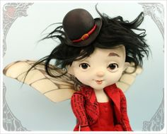 This Fairy Foreigner, 'Danda' traveling from the Filigree, wears a Scarlet Red 2 layer batiste circle dress with fitted bodice and little tailored tail coat in a Victorian Newsprint.  Adorable red polka dotted bloomers and silken knee socks in stripes and blooms. All Topped off with a bowler hat and sweet dancing shoes!