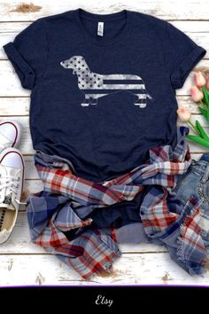 Dachshund T-shirt, American Flag Shirt, Vintage style Top, American Flag Tee, Fourth of July Patriotic graphic t shirt USA Merica t-shirt #affiliate #ad #usa #fourthofjuly independence day #patriotic #tshirt #dachshund #doxie #wienerdog #weeniedog #americanflag #graphictee #doglovers Flag Shirt, T Shirt, Vintage Style, Vintage Fashion, Weenie Dogs, Dachshunds, Cute Tops, American Flag, Graphic Tees