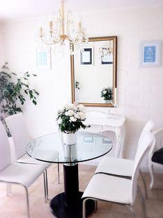 comedor eclectico: mesa redonda de cristal, lampara de araña, sillas blancas