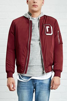 "A woven midweight bomber jacket featuring a stitched ""D"" chest patch, a high-polish zippered front, twin welt front pockets, a zippered utility pocket on the arm, and ribbed knit trim."