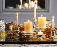 Assemble candlesticks, small bowls, and other vessels with reflective surfaces and place them on a mirror.  Fill them with white or ivory candles for a romantic centerpiece.