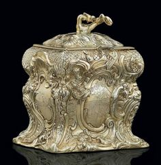 A REGENCY SILVER-GILT TEA CADDY MARK OF EDWARD FARRELL, LONDON, 1817 Shaped oblong, each side elaborately cast as a rococo cartouche, with fishscale and foliate scrolls and masks at each corner, two sides engraved with coat-of-arms, two sides engraved with crests, the cover chased with shells, grapes and roses, with dragon finial, marked on body and cover 5 1/8 in. H