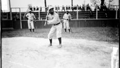 African American History / Black History. Portrait of Negro National League's Chicago American Giants baseball player Jones batting at home plate on a baseball field in Chicago, Illinois. Two teammates are standing on the field behind him. Spectators sitting in the top row of the bleachers are visible in the background. – 1911 – American Memory, Library of Congress
