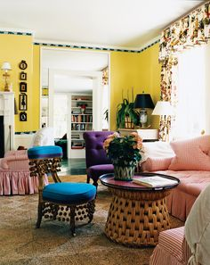 Use of bright color makes an otherwise traditional room—valences, gathered skirts—more modern, as citrine walls combine with candy-striped sofas and armchairs with hits of aqua and eggplant in interior designer Jeffrey Bilhuber's 17th-century home on Long Island.