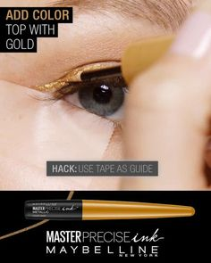Transform your basic cat eye using Maybelline's NEW Master Precise Ink metallic liquid liner. First, use black liner to line your lashes. Next,color the eye look bold by sweeping gold liner across the eyelid just above the black liner. Then, extend the gold line to create a cat eye. Hack this step with tape to guide a precise line. Finish the look by adding a stroke of teal liner above the gold liner.