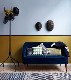 Salon design africain avec murs peinture couleur bleu, soubassement peinture jaune, ligne peinture noir, coussins tissu africain sur petit canapé bleu Monaco