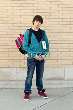 handsome teenage boy holding books. - Portrait of a handsome teenage boy holding books, Model: Ryan Kosmayer