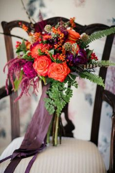 {Glamorous Bridal Florals Featuring: Hot Pink/Coral Circus Roses, Purple Mini Carnations, Scabiosa Pods, Red Hypericum Berries, Fuchsia Coxcomb, Cranberry Amaranthus, Green Sword Fern, Green Maiden Hair Fern, Hand Tied With Aubergine Ribbons···············································}
