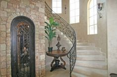 Curving Staircase with windows, beautiful metal railing, stone wall and a mysteriously cool door.