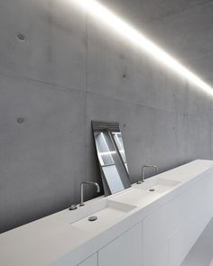 White corian bathroom with architectural concrete walls.