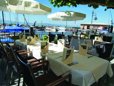Nehmen Sie Platz in unserem Restaurant mit Wintergarten, auf unserer großen Seeterrasse oder im neu gestalteten Garten mit Blick auf den Gondelhafen und die Schweizer Berge.