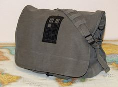 These military style bags are made of canvas and are super high quality.  The big area inside the bag has two dividers, perfect for books and tablets. The front has a space to hold pens and pencils and a flap that snaps to securely hold your supplies. Approximate dimensions are: 15 inches wide, 12 inches tall, and around 5 inches deep The strap from shoulder to bag is 21 inches with the strap itself being 42 inches long.