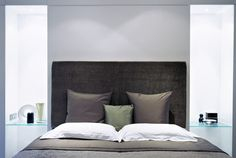 Upholstered headboard and glass bedside tables. The greys are nice and calm. I like mirrored tables too.