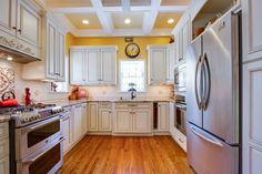 White kitchen in Transitional style  Recessed panel cabinets Executive Cabinetry in the Normandy door style in Maple with a Soft White Finish with Chocolate highlights.