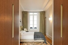A relaxing master bedroom with olive houndstooth curtains, a Beni Ouribane rug, and wooden closets