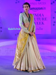 Ivory lehenga with floral print underskirt with a beautiful pale blue blouse embroidered with yellow flowers - LOVE IT! By Anju Modi at Amazon India Couture Week 2015