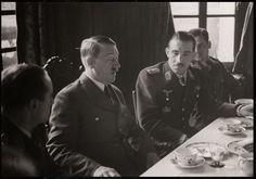 "Banquet to welcome the visit of Hitler to the headquarters of Jagdgeschwader 26 ( JG 26 ) "" Schlageter "" at Château de Bonnance in Abbeville , northern France , one day before Christmas 1940. From left to right : Hauptmann Rolf Pingel ( Gruppenkommandeur I. / JG 26 ) ; Adolf Hitler ( Führer und Reichskanzler ) , Oberstleutnant Adolf Galland ( Geschwaderkommodore JG 26 ) ; and Gerhard Hauptmann Schöpfel ( Gruppenkommandeur III . / JG 26 )"