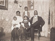 Virginia-born coachman Thomas A. Dillon and his wife, Margaret, a domestic servant and native of Newton, Massachusetts, pose in the parlor of their home at 4 Dewey Street with children Thomas, Margaret, and Mary in 1904. A poster on the wall commemorates President Theodore Roosevelt's visit to the Worcester Agricultural Fair in 1902