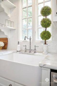 Lovely kitchen features a farmhouse sink and a deck mount faucet which stands below a window.