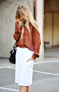 Rust color blouse with a bright white skirt, and a black purse.