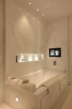 Niche lighting and reflected glow around bath. Warm, luxurious feel.
