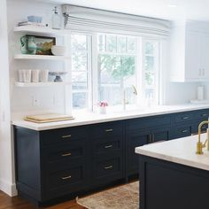 Love the open shelving next to the sink and the Roman shade.